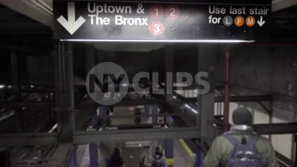 people descending downstairs to uptown 1 2 and 3 subway trains - sign for the Bronx in winter - 4K and 1080 HD in NYC