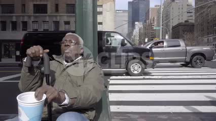 homeless black man with cane sitting on Park Ave corner shaking cup for help in 1080 HD in NYC