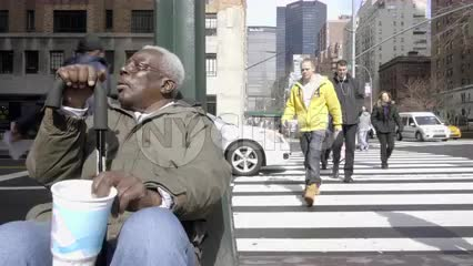 homeless elderly black man shaking cup on street with MetLife Building in background - 4K and 1080 HD in NYC