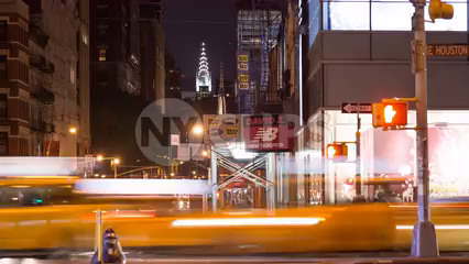 zooming back busy intersection of Broadway and Houston St, Chrysler Building view from SoHo in Manhattan - 4k timelapse NYC