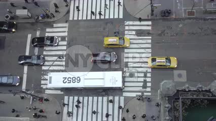 aerial view of cars driving in traffic and intersection crosswalk below in Midtown Manhattan in 1080 HD and 4K in NYC