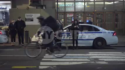 police car in front of Grand Central Terminal Station across crosswalk, woman on smart phone in 4K and 1080 HD in NYC
