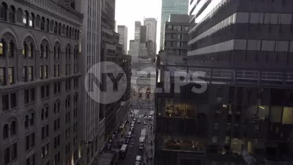 tilting down to cars in intersection below tall building in Midtown Manhattan NYC