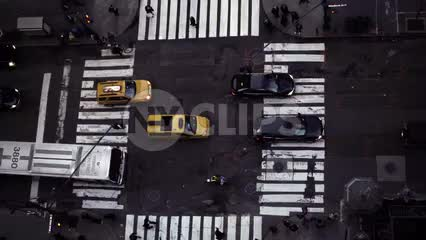 zooming out from overhead view of crosswalk street from tall building, cars driving in traffic in NYC