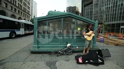 musician playing guitar in Cooper Square on summer day in Manhattan NYC