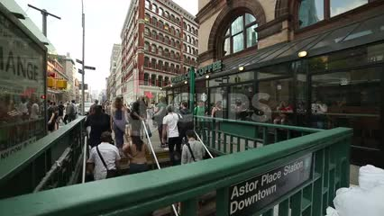 people exiting Astor Place subway station stairs with Starbucks Coffee House in Cooper Square on summer day in Manhattan NYC