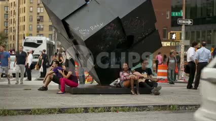 Cooper Square with hippies playing guitar - couple in love - famous cube sculpture in 1080 HD in NYC