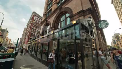 Starbucks in Cooper Square and Astor Place, panning on summer day with people outside in NYC