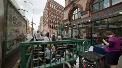 people exiting Astor Place subway station on summer day with Starbucks upstairs in NYC