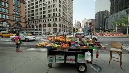 fruit stand in Cooper Square on summer day with famous cube sculpture in background