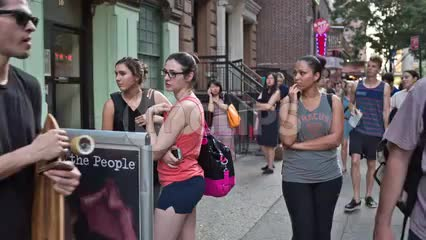 yoga sign in East Village with people entering studio in summer in Manhattan NYC
