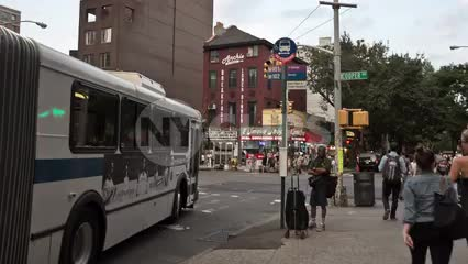 accordion bus departing at Cooper Square in East Village on summer day in Manhattan NYC