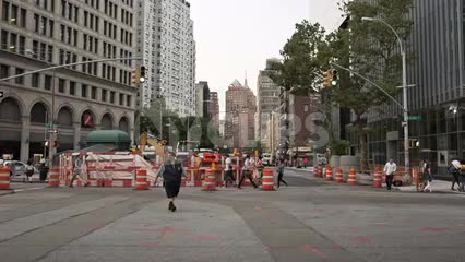 bus driver walking across Cooper Square with orange construction cones in Manhattan